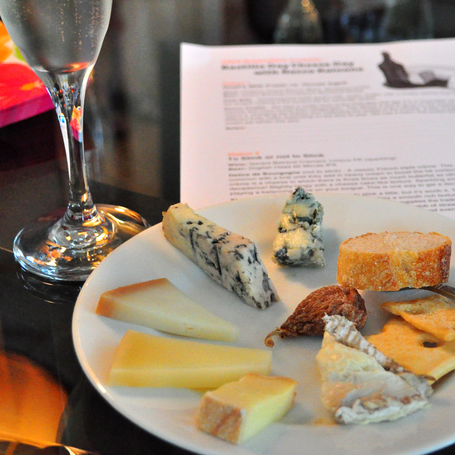 Elegant spread of cheeses on a small plate with champagne glass