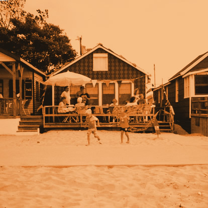 Vintage photo of a family barbecuing on the porch of a sandy bungalow