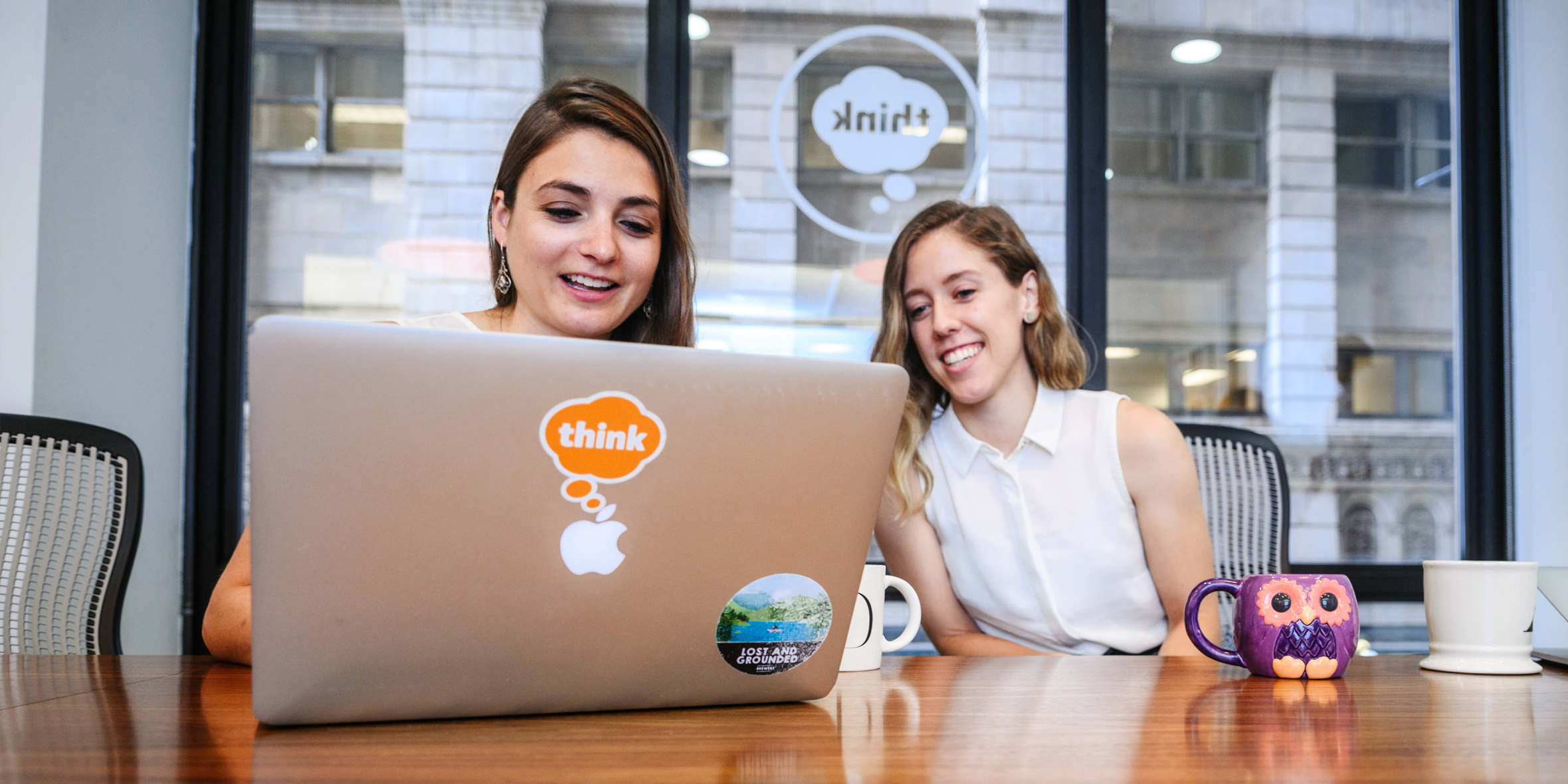 photo of two women looking at laptop