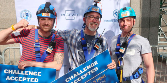 Photo of three men wearing repelling gear