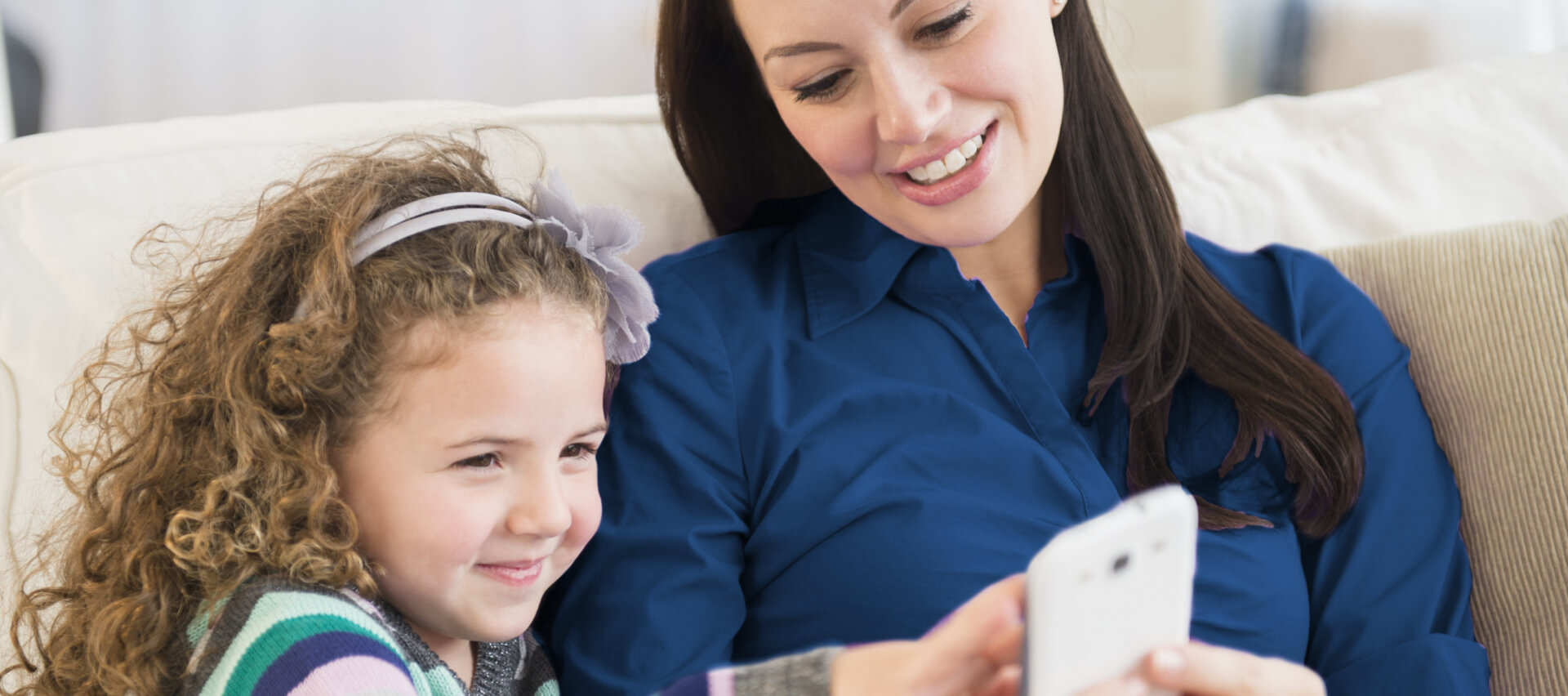 Woman and child playing on smartphone