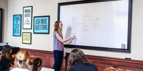 person at a white board leading a creative exercise