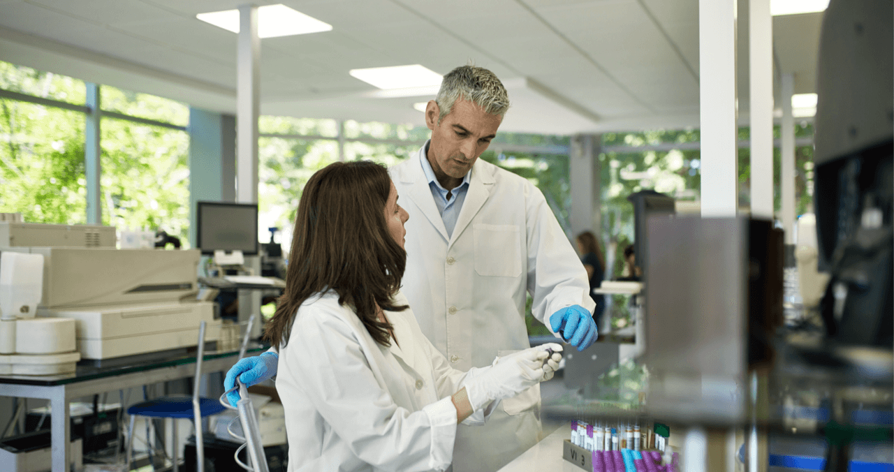 two HCPs look at a vial together in a lab